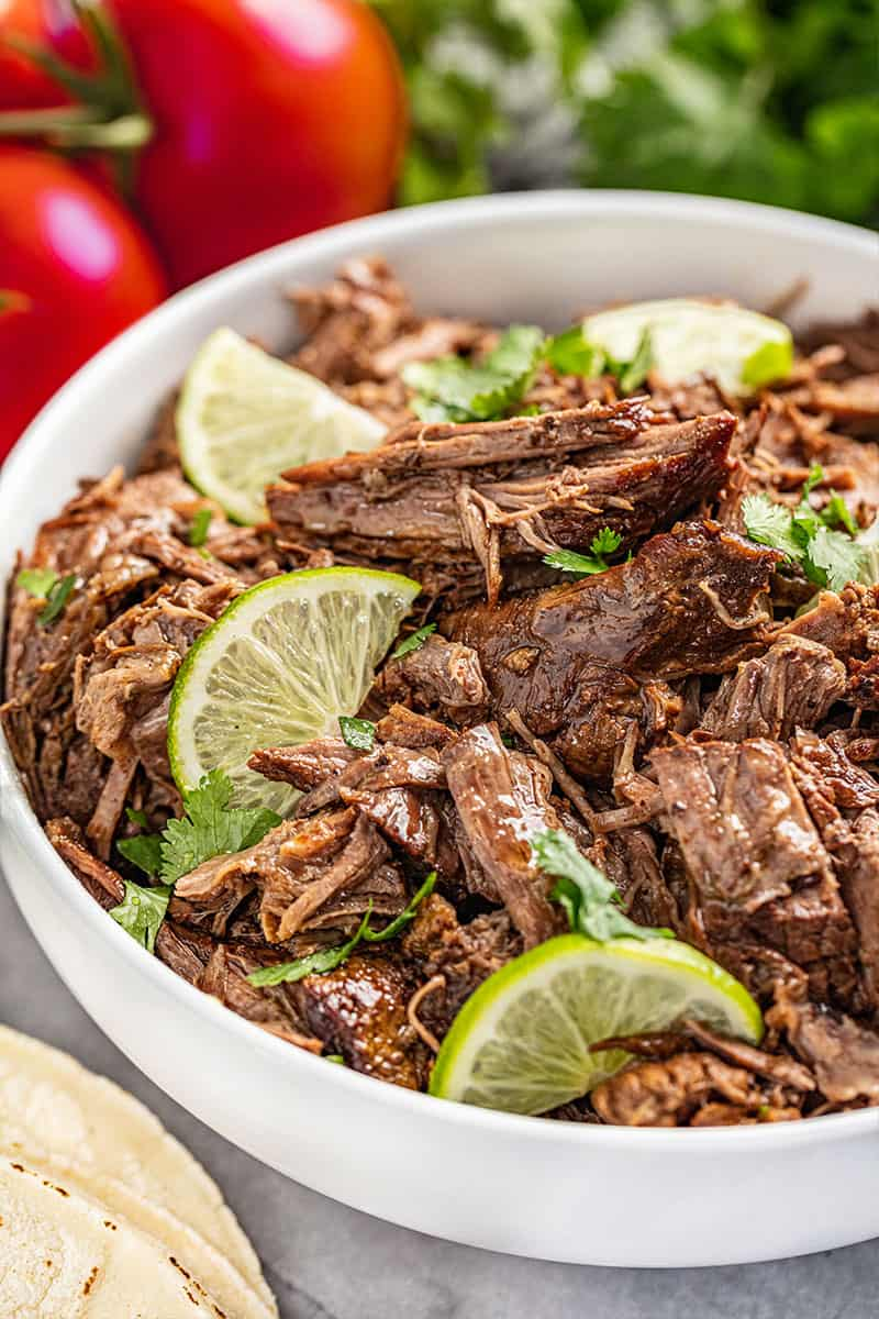 A white bowl filled with shredded beef.