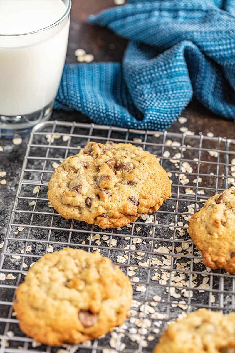 Oatmeal chocolate chip cookies on a wire rack with a glass of milk.
