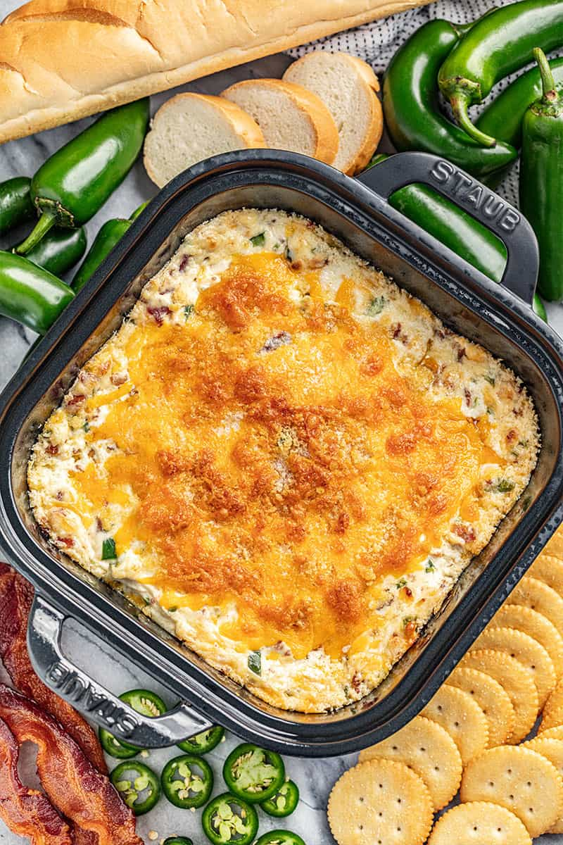 Overhead view of cheesy jalapeno popper dip in a baking dish.