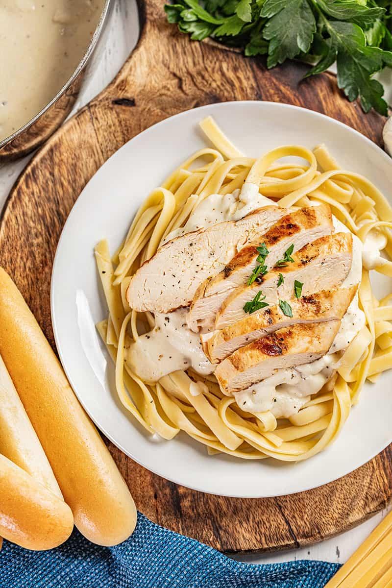 Classic chicken Alfredo with breadsticks.