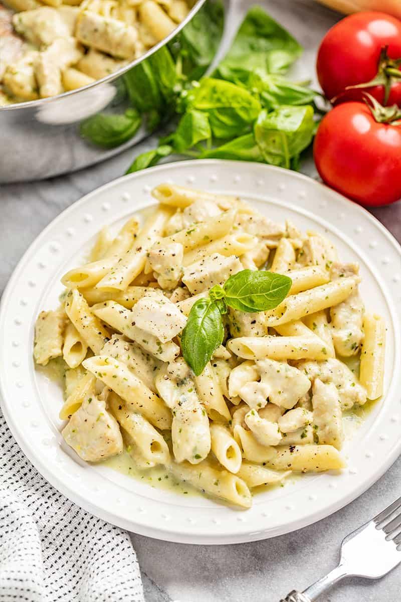 Kip pesto pasta op een witte bord met verse basilicum.