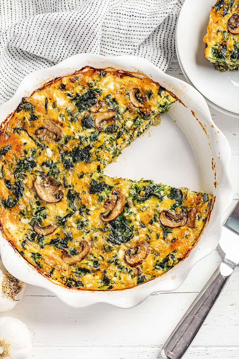 Crustless spinach quiche with one piece removed.