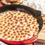 Simple s'mores dip in a red baking dish surrounded by marshmallows, graham crackers, and chocolate bars.