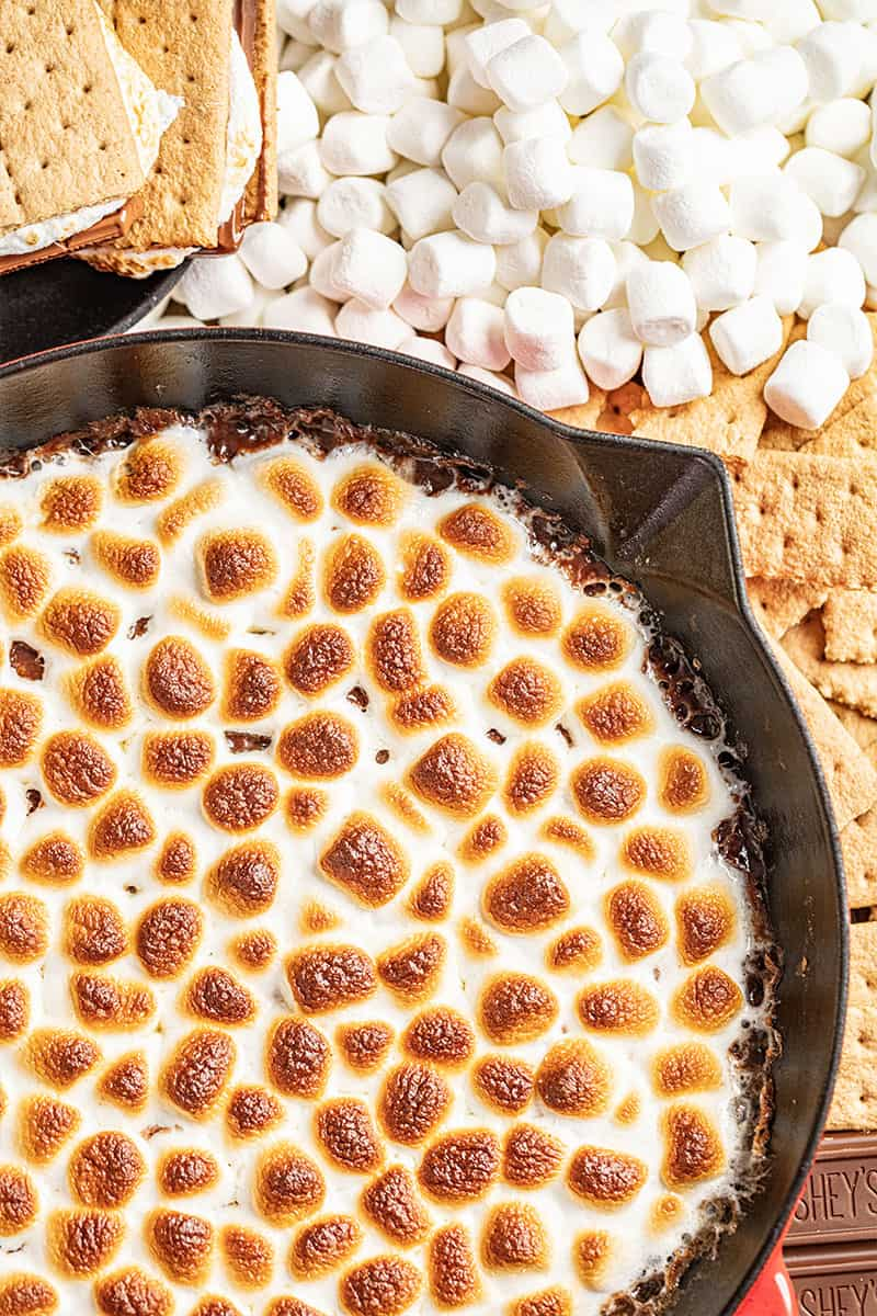 S'mores dip with marshmallows, graham crackers, and chocolate nearby.