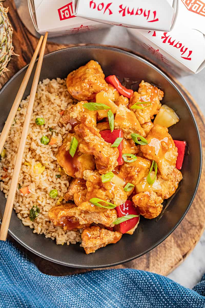 Sweet and sour chicken and rice in a black bowl.