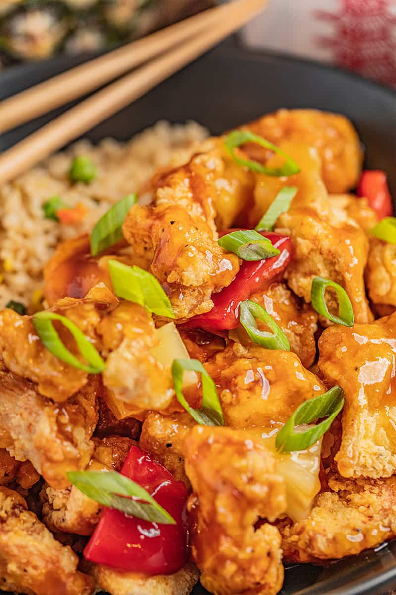 Close up view of sweet and sour chicken with sliced green onions on top.