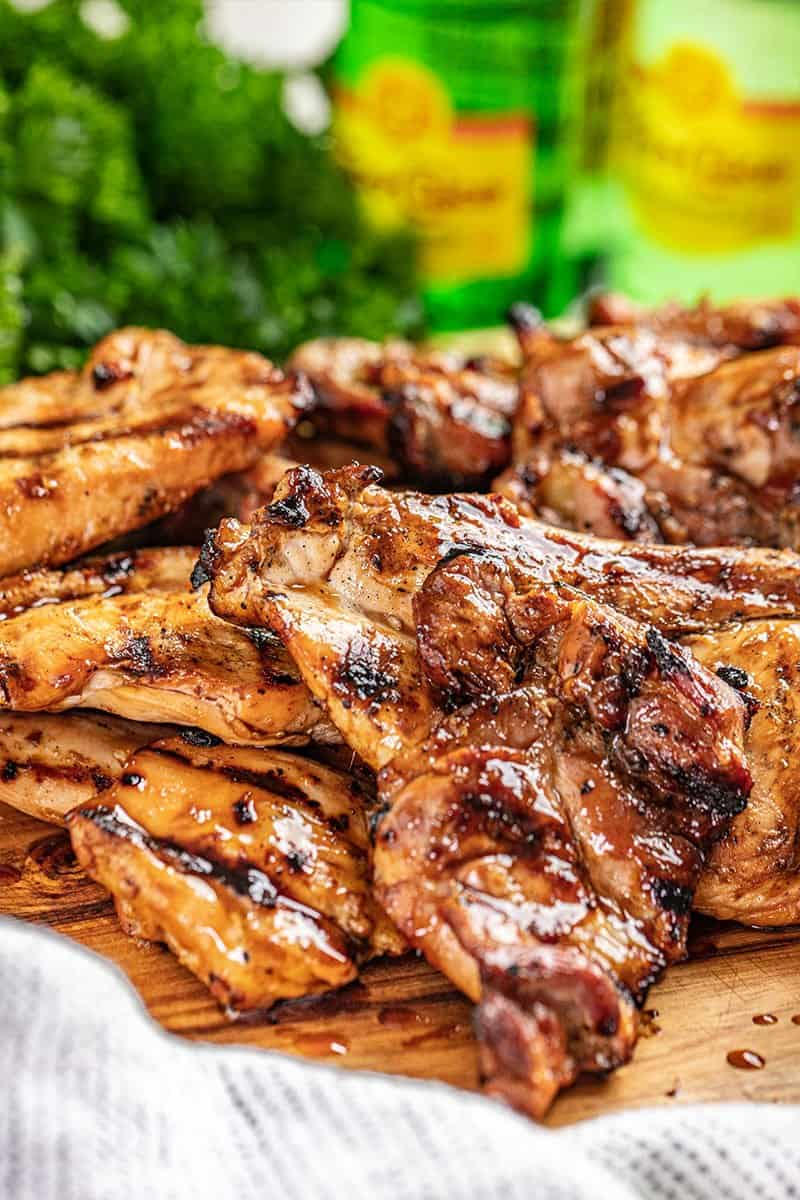 Juicy grilled chicken breast and thighs on a wood cutting board.