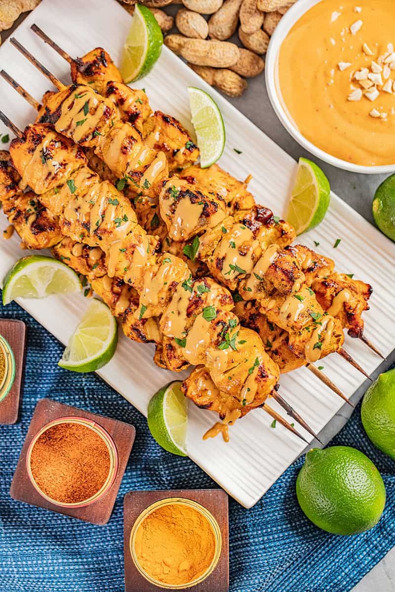 Overhead view of chicken satay with peanut sauce drizzled on top.