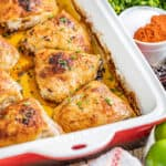 Chipotle and lime chicken thighs in a red and white baking dish.