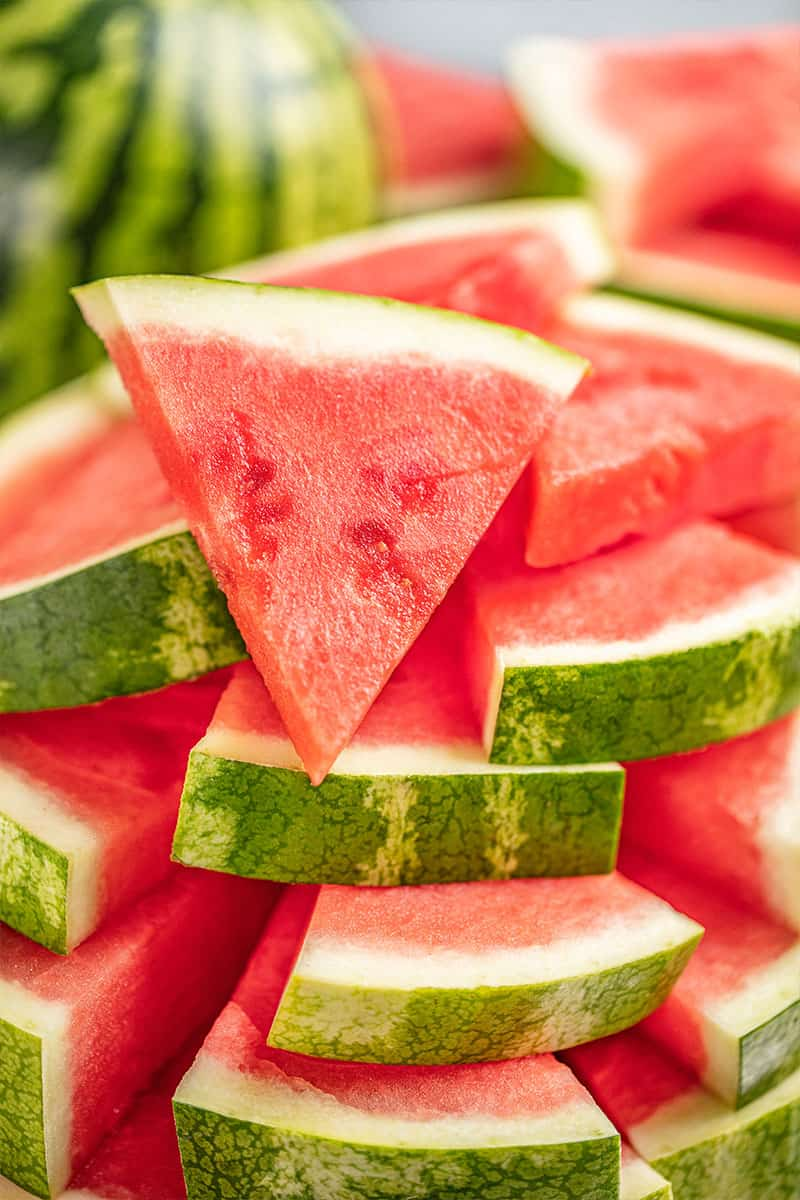 Large stack of watermelon cut into triangles.