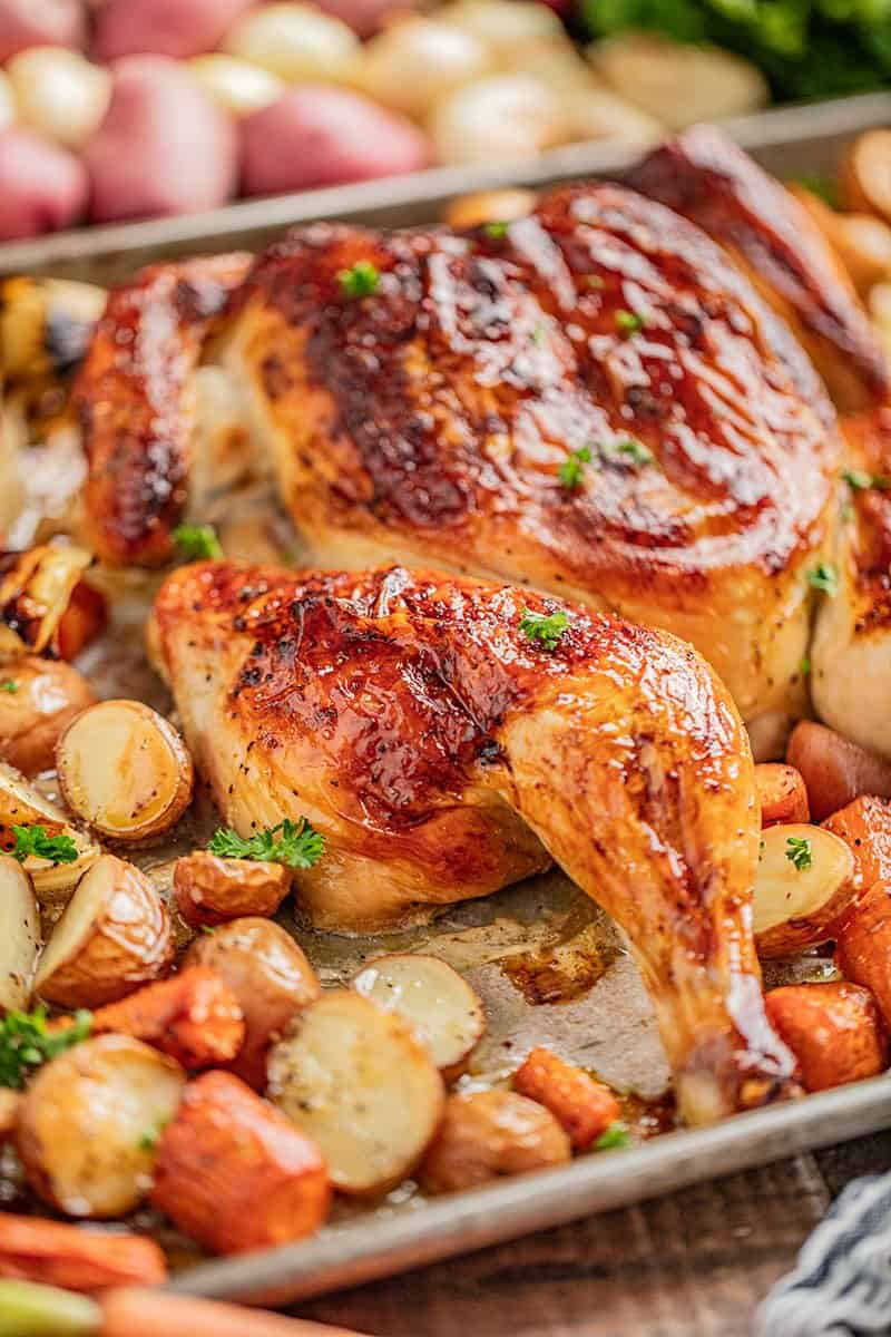 Spatchcock chicken on a baking sheet with carrots and potatoes.