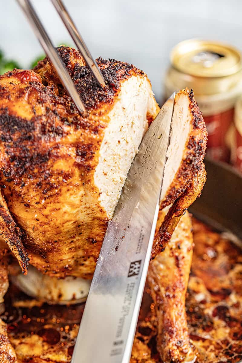 A knife slicing into a roasted whole beer can chicken.