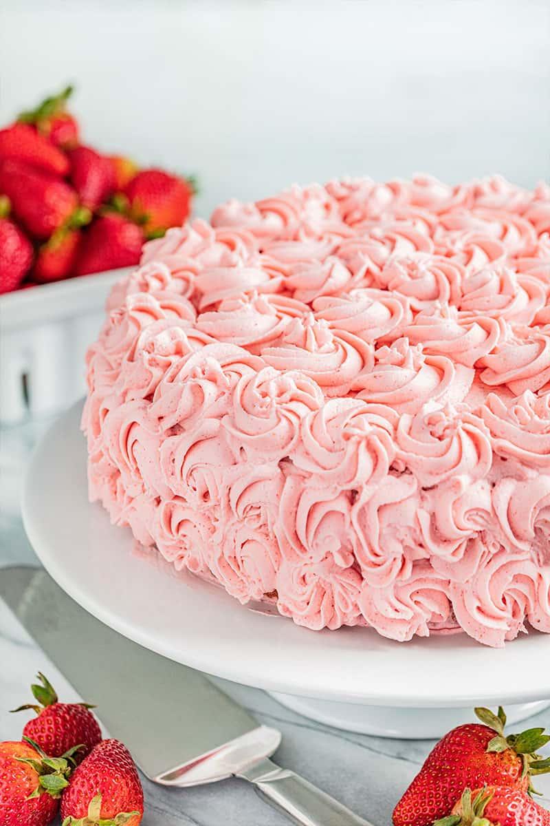 A whole strawberry cake on a cake stand.