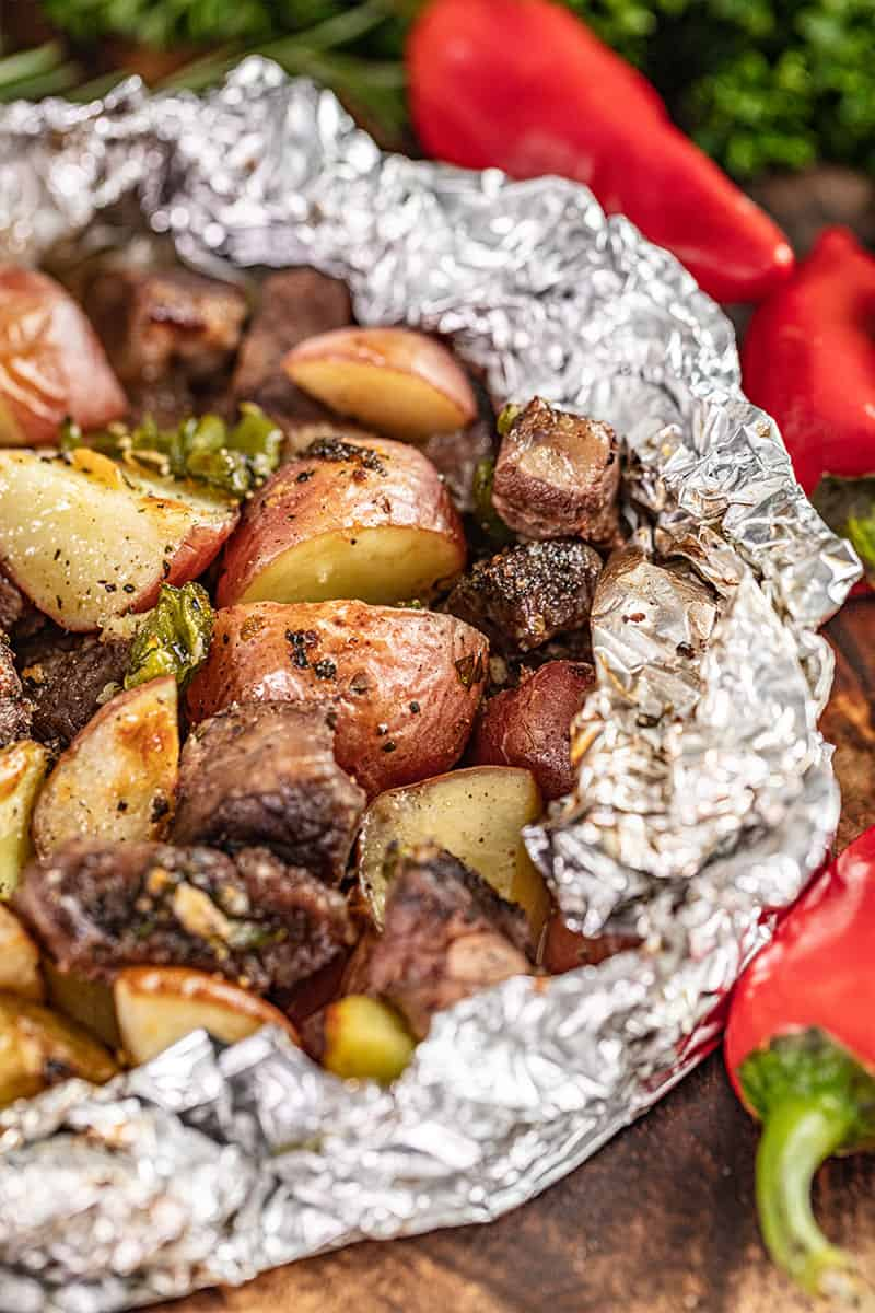 Close up view of a steak and potato foil packet.