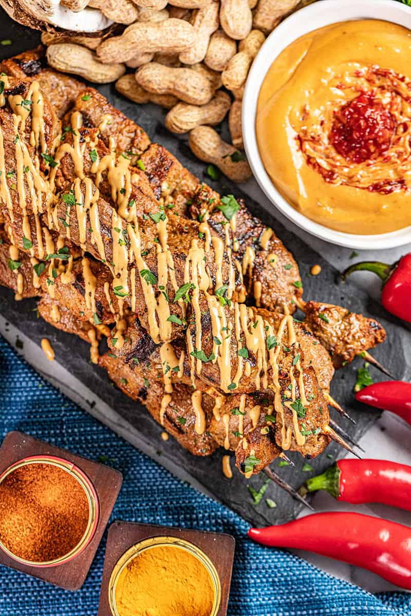 Overhead view of beef satay with peanut sauce.
