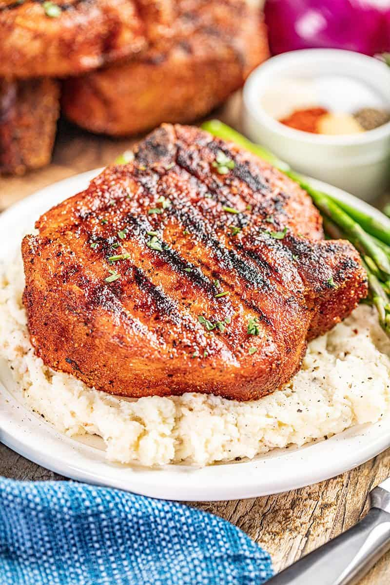 A smoked pork chop and mashed potatoes on a plate.