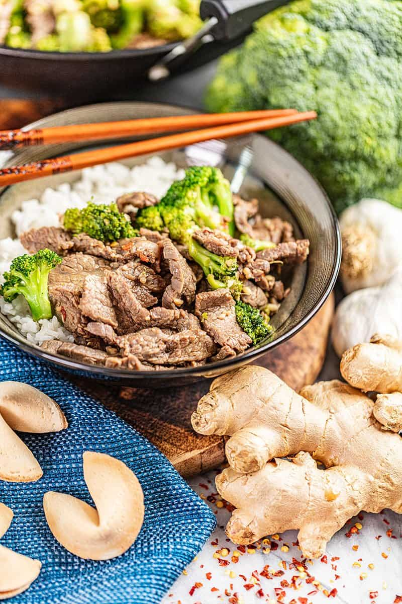 Takeout style beef and broccoli in a bowl with fresh ginger nearby.