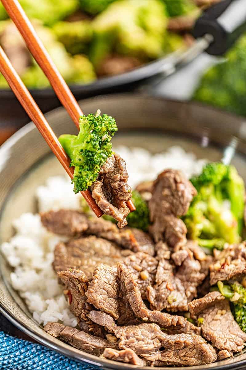 Chopsticks holding a piece of takeout style beef and broccoli.
