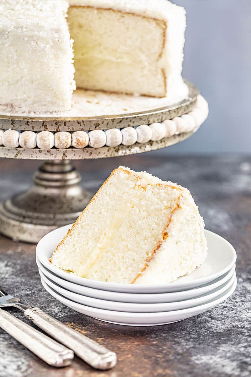 A slice removed from the most amazing white cake on a cake stand.