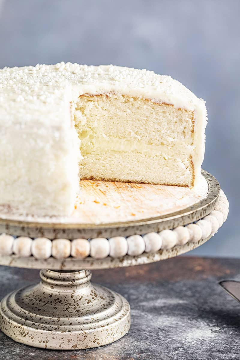 A white cake on a cake stand with one slice removed.