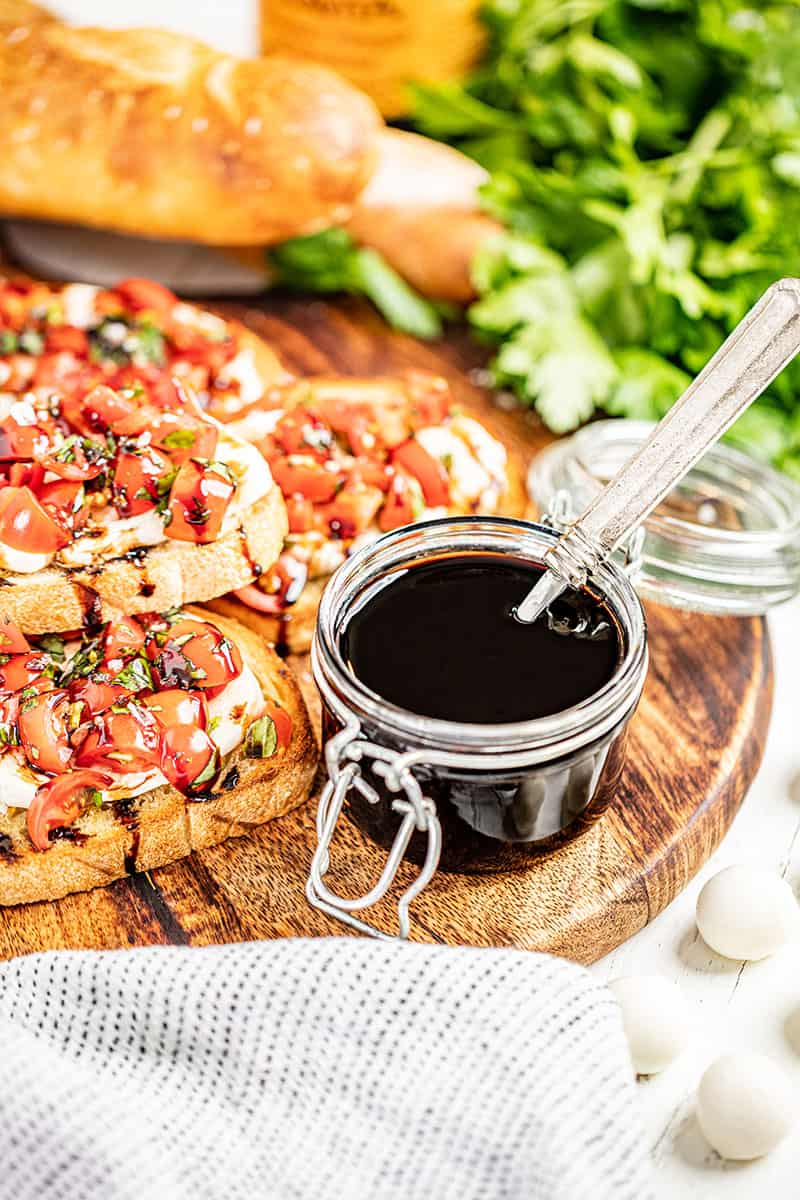 Balsamic glaze with a spoon in the jar.