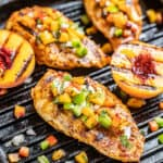 Chipotle peach glazed grilled chicken breasts on a pan.