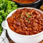Homemade pork and beans in a white bowl.