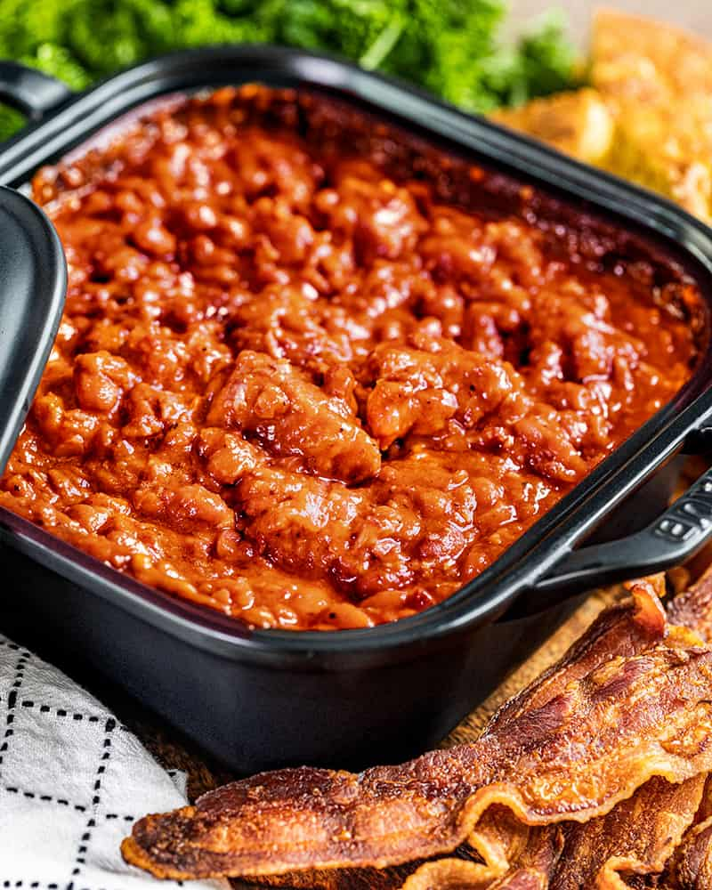 Homemade pork and beans in a square dish.
