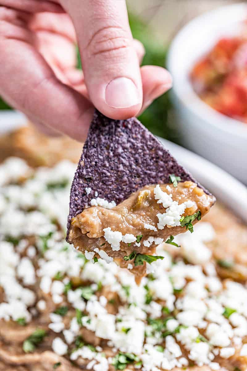 A hand holding a tortilla chip dipped in the most amazing bean dip.
