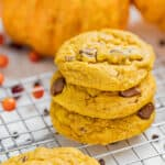 Close up view of a stack of pumpkin chocolate chip cookies on a cooling rack.