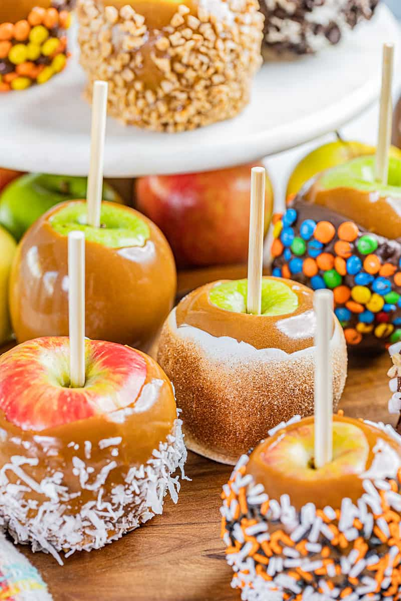 Homemade caramel apples with various toppings.