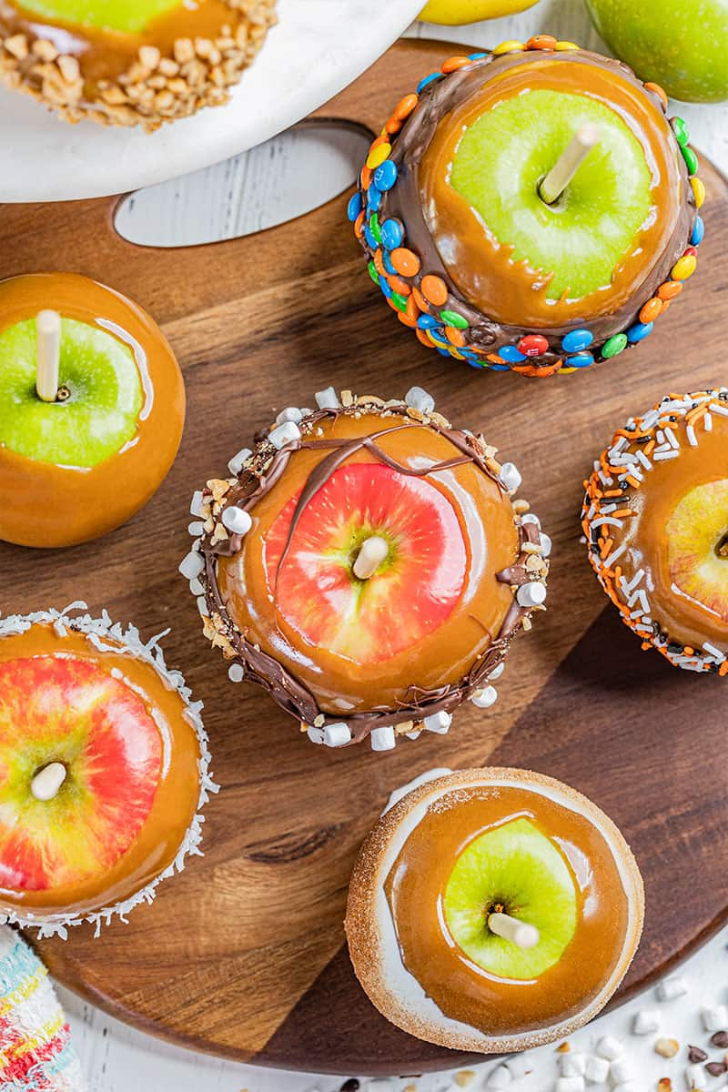 Overhead view of homemade caramel apples with various toppings.