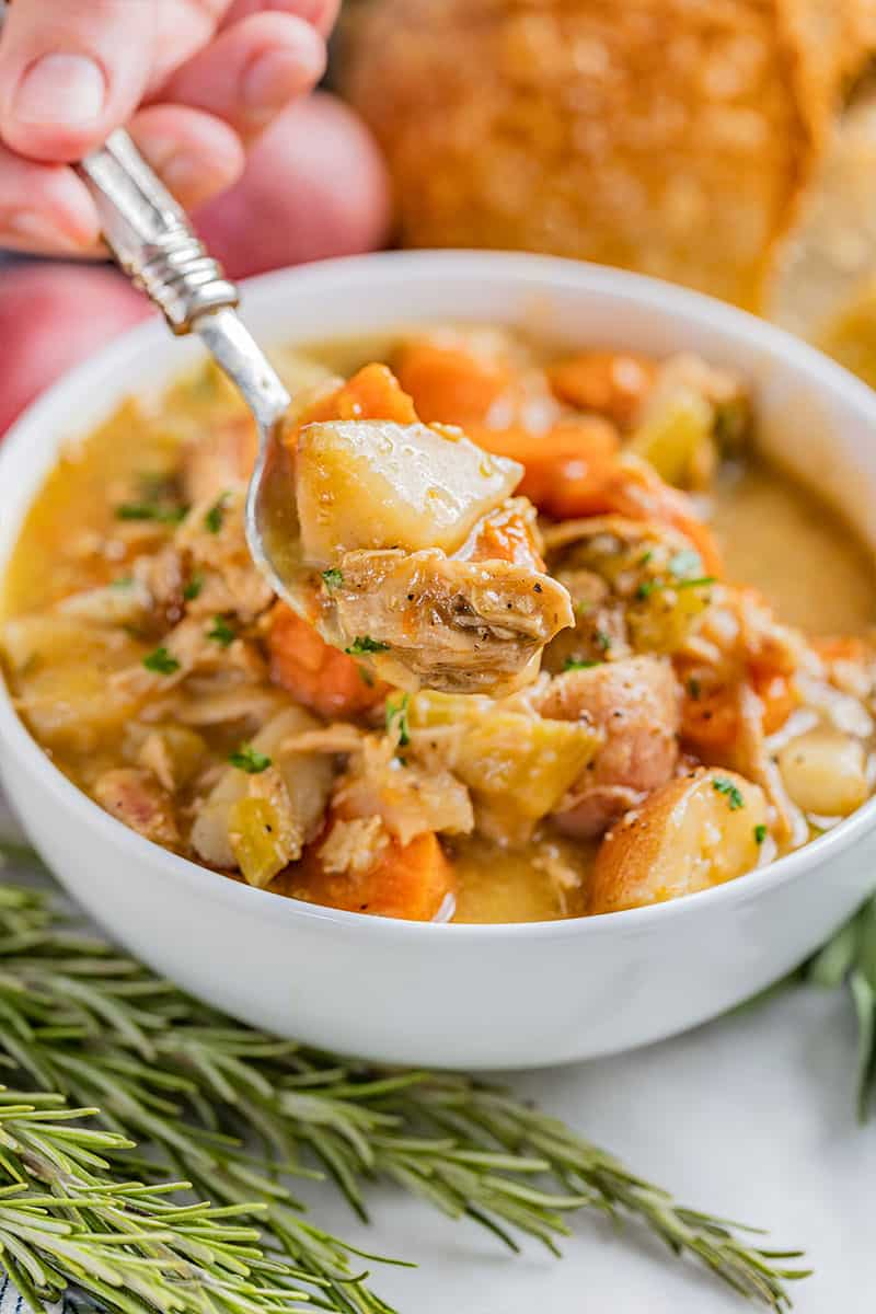 A spoon filled with old fashioned chicken stew being held over a full bowl.
