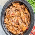 Overhead view of shredded sweet pork in a slow cooker.