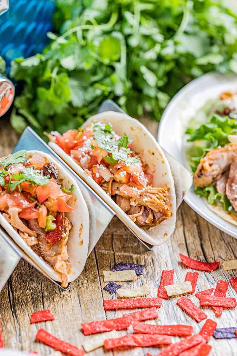 Sweet shredded pork in tacos in a taco holder.